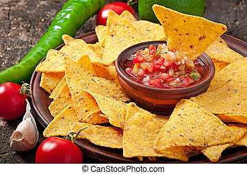 Mexican nacho chips and salsa dip in bowl on wooden...