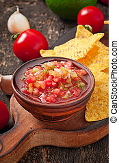 Mexican nacho chips and salsa dip in bowl on wooden ...