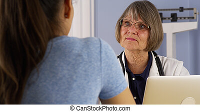 Mexican patient talking to Senior doctor in office