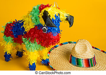 Mexican pinata and sombrero on yellow
