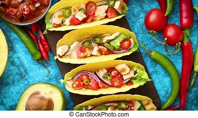 Mexican taco with chicken meat, jalapeno, fresh vegetables served with guacamole and tomato salsa. Latin american food. Placed on blue table.