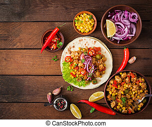 Mexican tacos with meat, corn and olives on wooden...