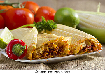 Mexican tamales on plate. - Mexican tamale wrapped in corn ...
