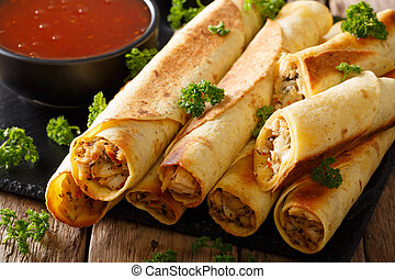 Mexican taquitos with chicken and chili sauce close-up. ...