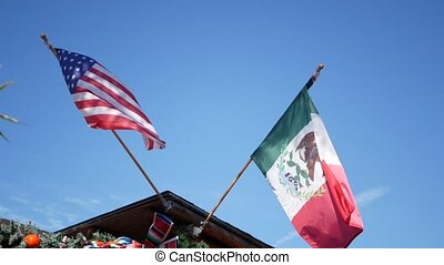 Mexican tricolor and American flag waving on wind. Two national icons of Mexico and United States against sky, San Diego, California, USA. Political symbol of border, relationship and togetherness