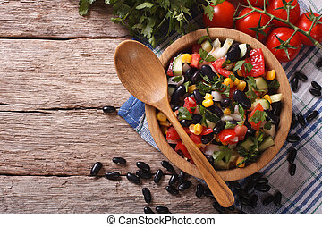 Mexican vegetable salad in a wooden bowl, close-up...