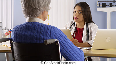 Mexican woman doctor talking with senior patient