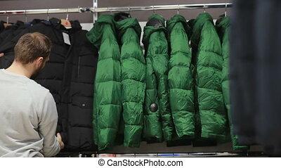 mezza età, uomo, chooses, uno, riscaldare, giacca, in, negozio