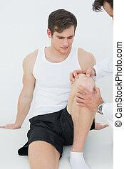mißfallen, junger mann, bekommen, seine, knie, untersucht