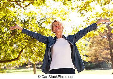 mi, âge, femme, à, bras étendus, dehors