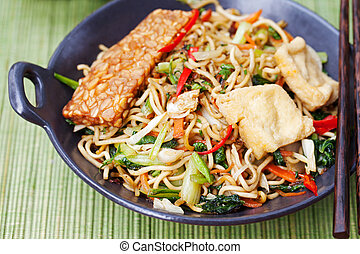 Mi goreng,mee goreng Indonesian cuisine, spicy stir fried noodles with tempeh and assortment sauces