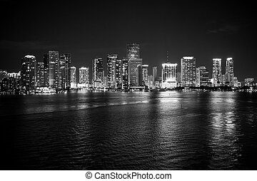 Miami city skyline panorama at night, usa. Skyscrapers illumination reflect on sea water in dusk. Architecture, structure, design. Building, construction, development. Wanderlust, travel, discovery