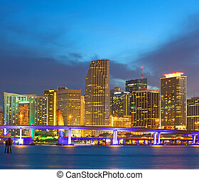 Miami Florida USA, sunset or sunrise over the city skyline of downtown business and residential illuminated buildings, with colorful clouds and reflections in the water of Biscayne Bay,