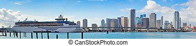 Miami skyscrapers with bridge over sea in the day.