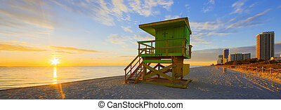 Miami South Beach sunrise with lifeguard tower and coastline...