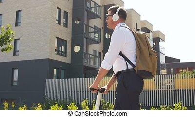 miasto, biznesmen, słuchawki, hulajnoga, jeżdżenie