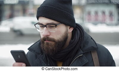 miasto, człowiek, używa, smartphone, i, pijąca herbata, na, zima, ulica