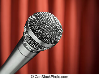 Mic on stage - A dynamic microphone over a red background.