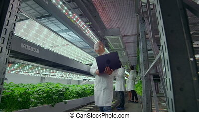 Microbiology in white coats go on a modern farm with laptops...