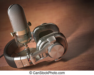 Microphone and headphones on the wooden table. Retro vintage style background. Radio concept