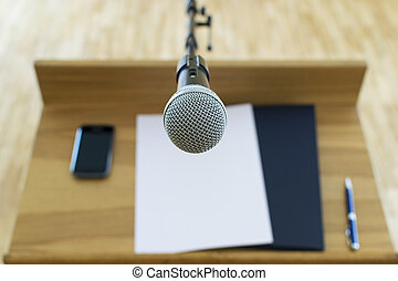 Microphone at the speech podium. Mobile phone, documents, pen. First person view. Shallow depth of field