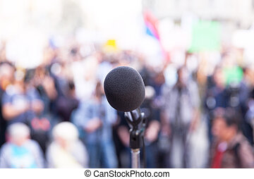 Microphone in focus, against blurred crowd - Demonstration....