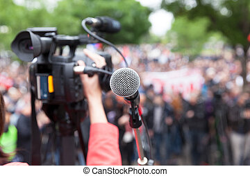 Microphone in focus against blurred crowd. Filming protest....