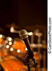 Microphone on stand with studio lights. There is a drum set on the background
