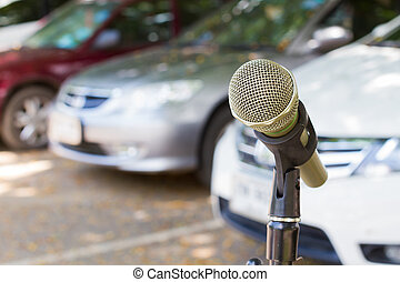 microphone on a stand with blurred vehicles in car park...