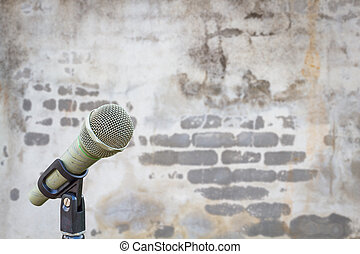 microphone on defocused blurred concrete wall with texture of bricks and grunge background