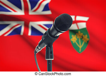 Microphone on stand with Canadian province flag on...