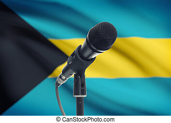 Microphone on stand with national flag on background - Bahamas