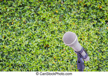 microphone on the background of blurred green leaves or bush. soft focus .shallow depth of field.