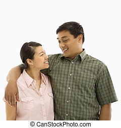 Mid adult Asian couple standing with arms around eachother and smiling at one another.