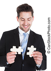 Mid Adult Businessman Holding Puzzle Pieces