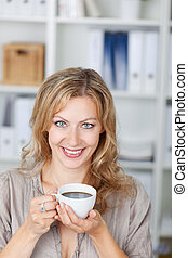 Mid Adult Businesswoman Holding Coffee Cup In Office