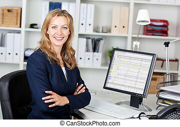 Mid Adult Businesswoman With Computer At Desk - Portrait of...