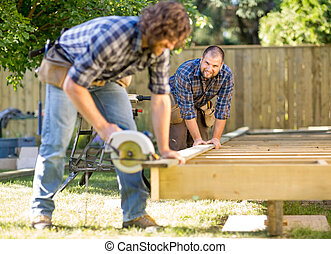 Mid adult carpenter looking at coworker while assisting him in cutting wood with handheld saw