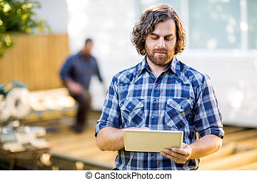 Mid adult carpenter using digital tablet with coworker working in background at construction site