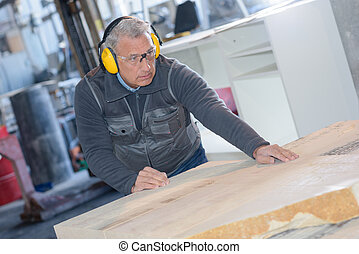 mid adult carpenter using tablesaw to cut wood in workshop
