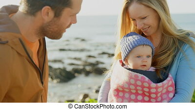 Mid adult caucasian parents kissing baby at beach on a sunny...