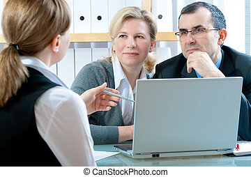 mid adult couple meeting with financial planner or advisor