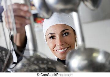chef - mid adult female chef taking kitchen utensil