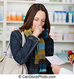 Mid adult female customer coughing while looking at pharmacist's hands holding prescription paper and medicine bottle in pharmacy