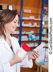 Mid adult female pharmacist holding medicine bottle while reading prescription paper in pharmacy