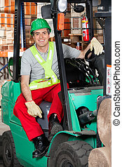 Mid Adult Forklift Driver At Warehouse - Portrait of mid...
