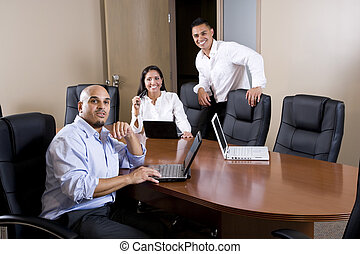 Mid-adult Hispanic office workers in boardroom meeting with...