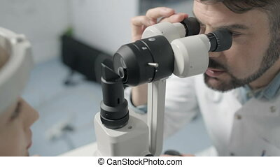 Mid adult male optometrist examining patient's eye - Defect...
