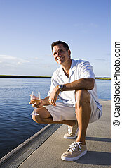 Mid-adult man on dock by water enjoying drink