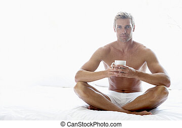 Mid Adult Man Sitting On Bed And Drinking Coffee